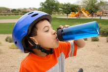 Child wearing bike helmet drinking water
